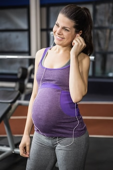 Kobieta w ciąży słucha muzyki przy gym