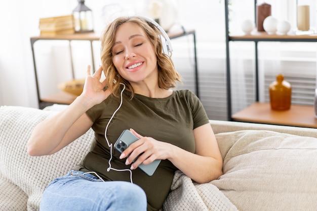 Kobieta w ciąży słucha muzyki w słuchawkach leżąc na kanapie trzymając w ręku smartfon zrelaksuj się ciesz się atmosferą
