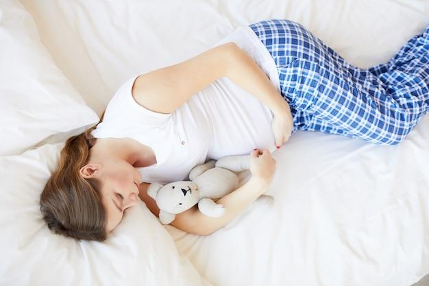 Kobieta w ciąży śpi w łóżku