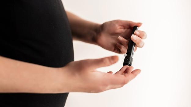 Kobieta w ciąży sprawdza poziom cukru we krwi. cukrzyca ciężarnych. zdrowie ciąży. test na cukrzycę