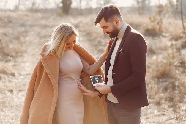Kobieta w ciąży stoi w parku z mężem