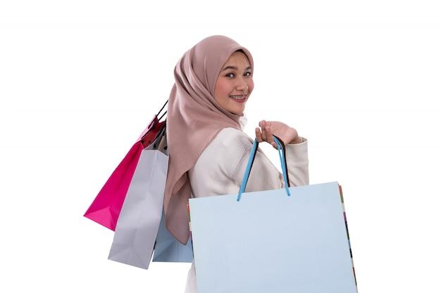Kobieta w ciąży stoją niosąc torby na zakupy
