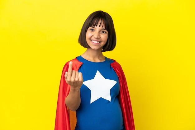 Kobieta w ciąży super hero na żółtym tle robi nadchodzący gest