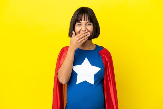 Kobieta w ciąży super hero na żółtym tle szczęśliwa i uśmiechnięta zakrywająca usta dłonią