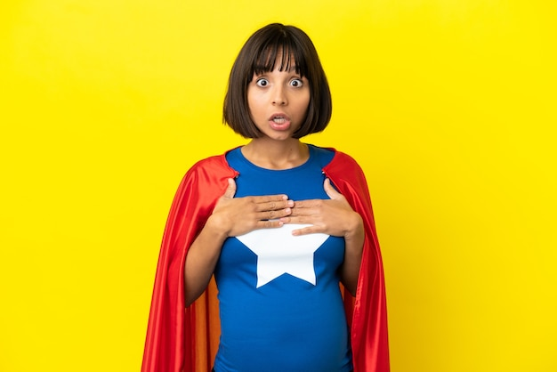Kobieta w ciąży super hero na żółtym tle zaskoczona i zszokowana, patrząc w prawo