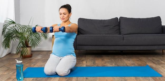 Kobieta w ciąży trenująca z ciężarami w domu