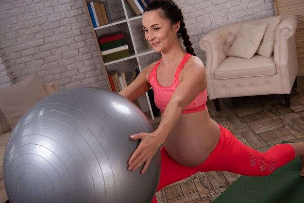 Kobieta w ciąży trenuje brzucha z piłką w domu