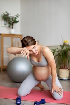 Kobieta w ciąży trenuje w domu