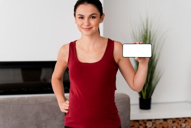 Kobieta w ciąży trzyma białą kartę w ręku