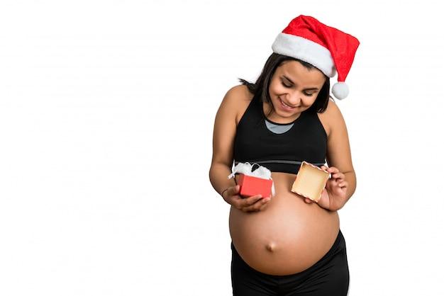 Kobieta w ciąży trzyma boże narodzenie prezenta pudełko.