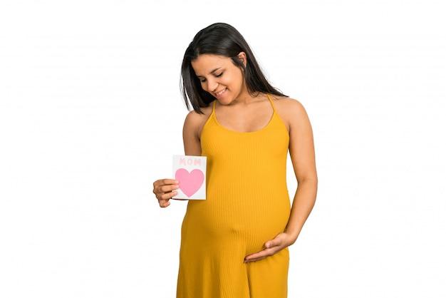 Kobieta w ciąży trzyma kartkę z życzeniami.