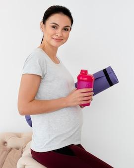 Kobieta w ciąży trzyma matę fitness i butelkę wody