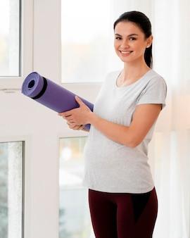 Kobieta w ciąży trzyma matę fitness