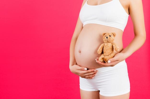 Kobieta w ciąży trzyma misia