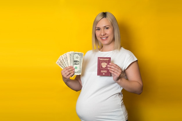 Kobieta w ciąży trzyma paszport z pieniądze. korzyści dla kobiet w ciąży, na żółtej ścianie
