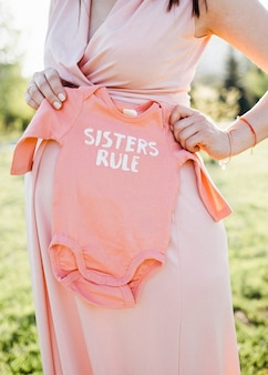 Kobieta w ciąży trzyma różowe ciało dla swojej przyszłej córeczki