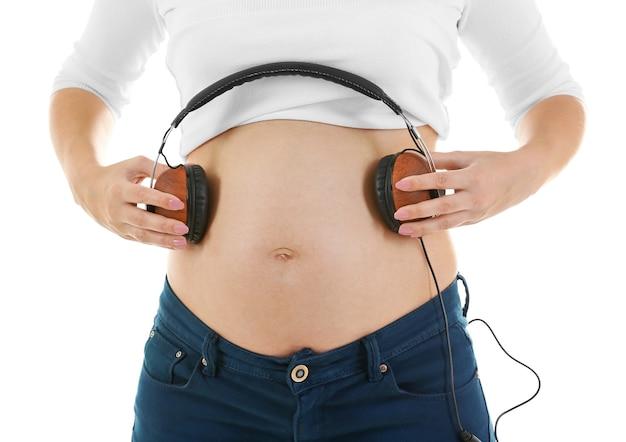 Kobieta w ciąży trzyma słuchawki na brzuchu, na białym tle