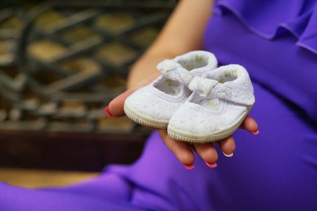 Kobieta w ciąży trzymając buty dziecięce na dłoni w pobliżu brzucha
