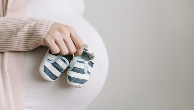 Kobieta w ciąży trzymająca buty dla noworodka