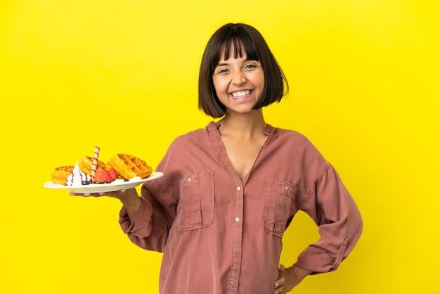 Kobieta w ciąży trzymająca gofry izolowane na żółtym tle patrząc z boku
