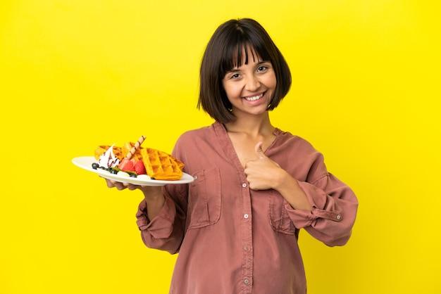 Kobieta w ciąży trzymająca gofry odizolowane na żółtym tle dająca gest kciuka w górę