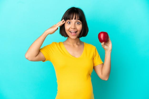 Kobieta w ciąży trzymająca jabłko na białym tle na niebieskim tle z wyrazem zaskoczenia