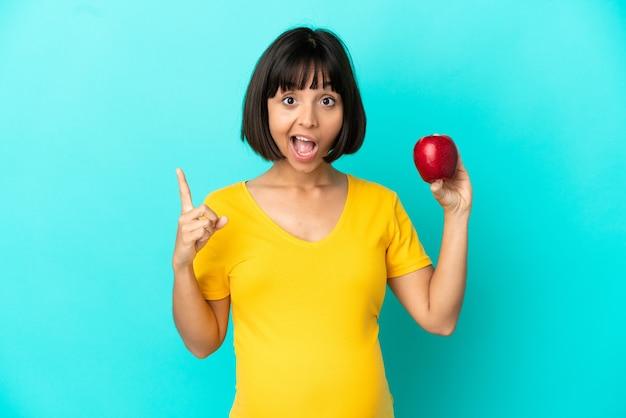 Kobieta w ciąży trzymająca jabłko na białym tle na niebieskim tle zamierzająca zrealizować rozwiązanie, podnosząc palec w górę