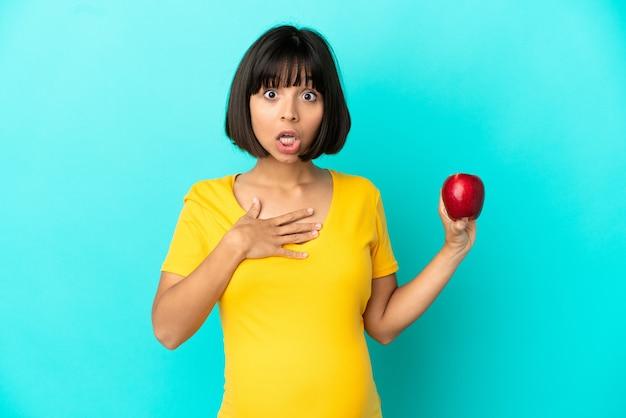 Kobieta w ciąży trzymająca jabłko na białym tle na niebieskim tle zaskoczona i zszokowana, patrząc w prawo