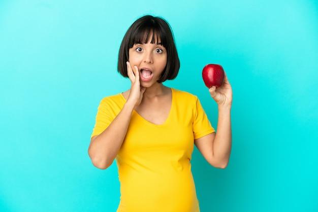 Kobieta w ciąży trzymająca jabłko na białym tle na niebieskim tle ze zdziwieniem i zszokowanym wyrazem twarzy