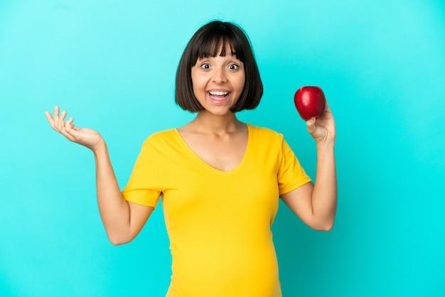 Kobieta w ciąży trzymająca jabłko na białym tle na niebieskim tle ze zszokowanym wyrazem twarzy