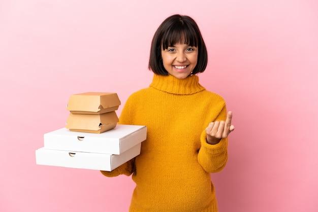 Kobieta w ciąży trzymająca pizze i hamburgery na białym tle na różowym tle robi gest nadchodzący