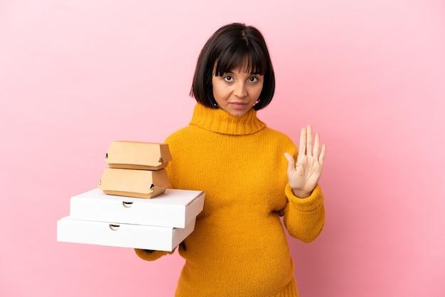 Kobieta w ciąży trzymająca pizze i hamburgery odizolowane na różowym tle wykonując gest zatrzymania