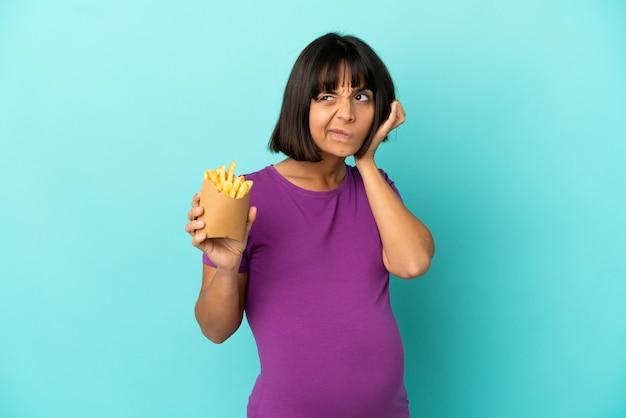 Kobieta w ciąży trzymająca smażone frytki na białym tle sfrustrowana i zakrywająca uszy