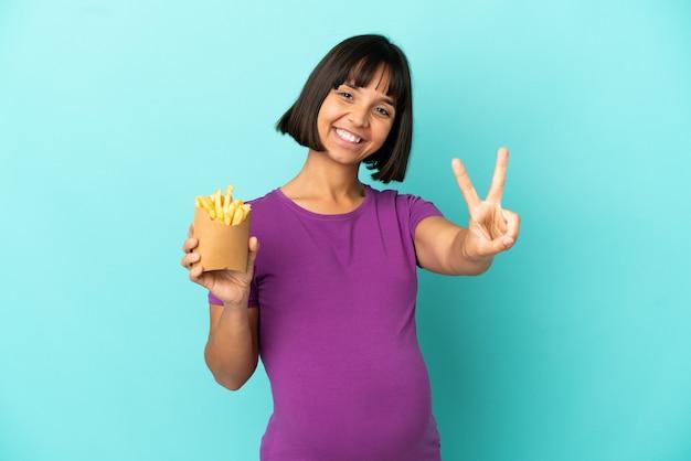 Kobieta w ciąży trzymająca smażone frytki na białym tle, uśmiechnięta i pokazująca znak zwycięstwa