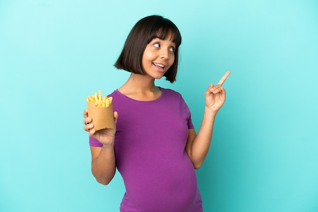 Kobieta w ciąży trzymająca smażone frytki na białym tle, wskazując na świetny pomysł
