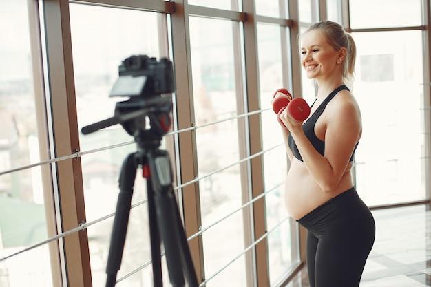 Kobieta w ciąży uprawia sport z dambels