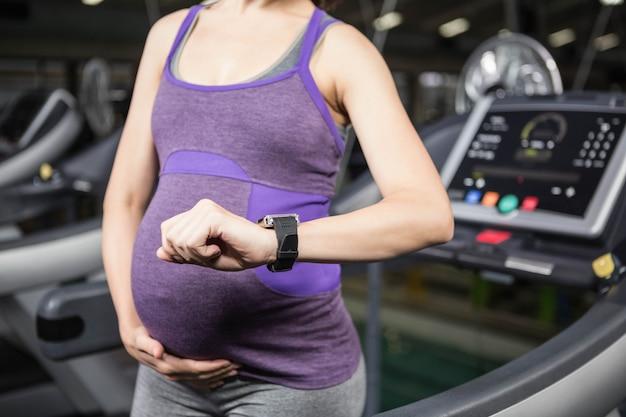 Kobieta w ciąży używa mądrze urządzenie dla sprawności fizycznej w gym