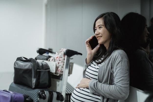 Kobieta w ciąży używa telefonów komórkowych do dzwonienia przed odlotem