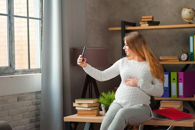 Kobieta w ciąży w białym swetrze.