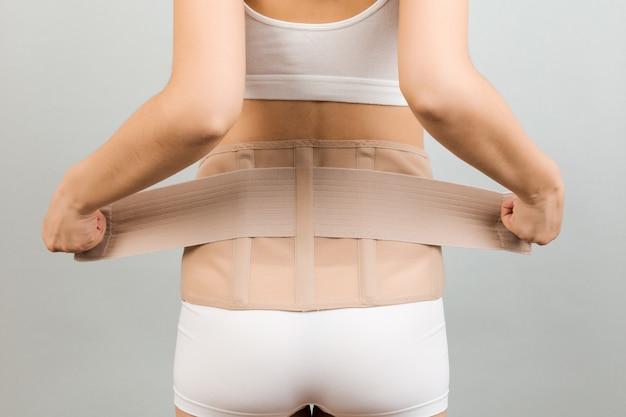 Kobieta w ciąży w bieliźnie ubierającej gorset ortopedyczny
