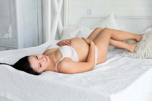 Kobieta w ciąży w bieliźnie zostaje pozowanie w łóżku