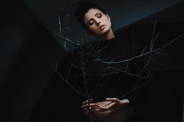 Kobieta w ciąży w czarne ubrania stoi pod szare ściany i posiada gałąź drzewa