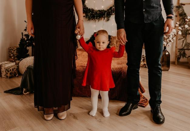Kobieta w ciąży w czarnej długiej sukni z mężem w czarnym garniturze z dzieckiem w czerwonej sukience. świąteczny poranek. noworoczne wnętrze. obchody walentynek