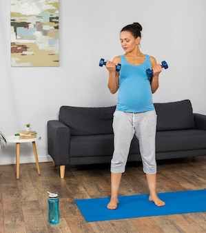 Kobieta w ciąży w domu trening na macie do ćwiczeń z ciężarami