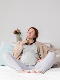 Kobieta w ciąży w domu w łóżku
