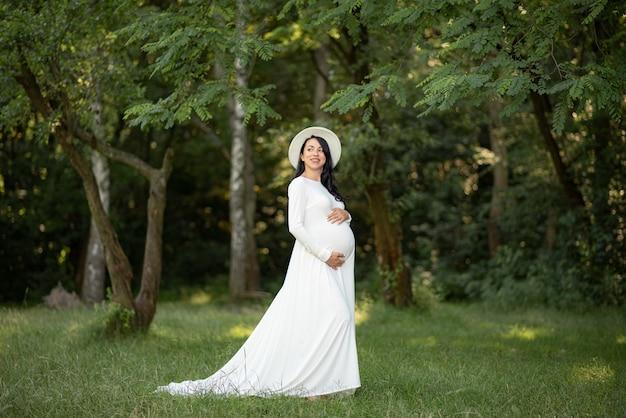Kobieta w ciąży w kapeluszu, pozowanie w białej sukni na zielonych drzewach.