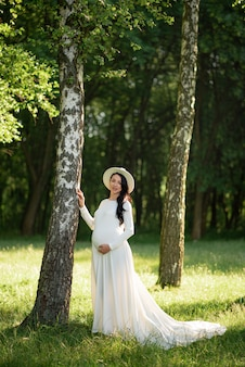 Kobieta w ciąży w kapeluszu pozuje w białej sukni z zielonymi drzewami.