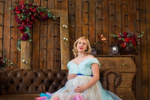 Kobieta w ciąży w kolorowej bufiastej sukni na ścianie drewnianego wnętrza w kwiecistym lofcie. szczęśliwa ciąża
