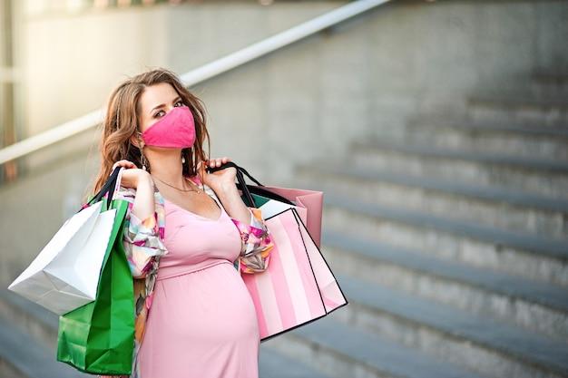 Kobieta w ciąży w masce ochronnej idzie z paczkami w pobliżu centrum handlowego.