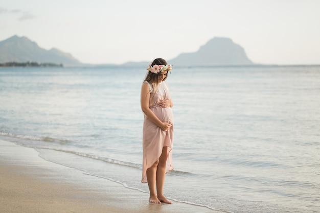 Kobieta w ciąży w pięknej sukni na oceanie.